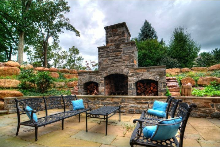 Designing outdoor fireplaces like the one at this Newtown Square home means cozy evenings in the yard on chilly nights.