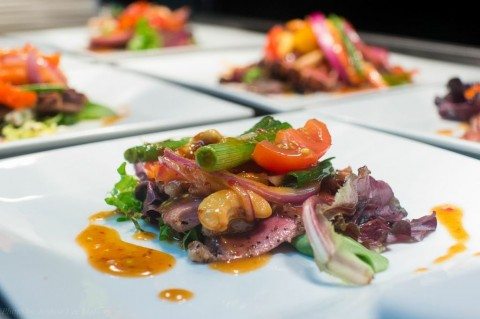 Seared Margret duck with peppers, onion, tomatoes and cashews served a sweet chili vinaigrette