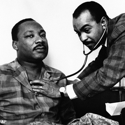 Dr. Martin Luther King, Jr., head of the Southern Christian Leadership Conference, sits up in his hotel room bed in Philadelphia, Feb. 10, 1968 while being examined by Dr. Walter Lomax, a Philadelphia physician. On the physician's orders Dr. King canceled his appointments and speaking engagements for the day because of a throat ailment. Dr. King has been in Philadelphia for past two days recruiting followers for proposed march on the nation's capital in April. (AP Photo)