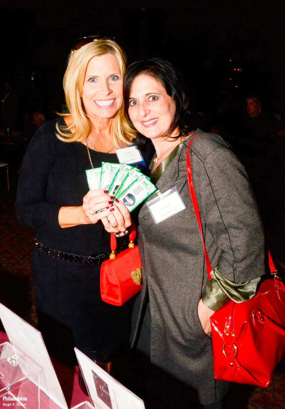 "Tickets for the charity event were $75, and  each guest was given $400 to play at the tables. Below, from left: host of <em>It's Your Call with Lynn Doyle<e/m> Lynn Doyle with the funny money, and Gina Rubel of Furia Rubel Communications, Inc., check out the silent auction items that ranged from trips, to dinner to a signed hockey stick by Scott Hartnell plus balls signed by Roy ""Doc"" Halladay and Cole Hamels."