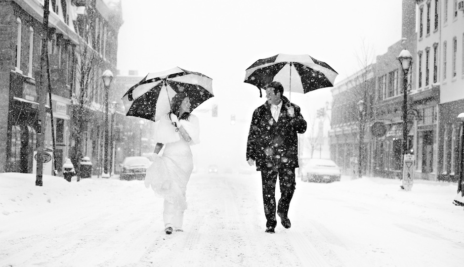 Gretchen and Steve walk along a snow-covered Bridge Street in Phoenixville near their winter wedding at the Phoenixville Foundry. Photo by Phillp Gabriel Photography.