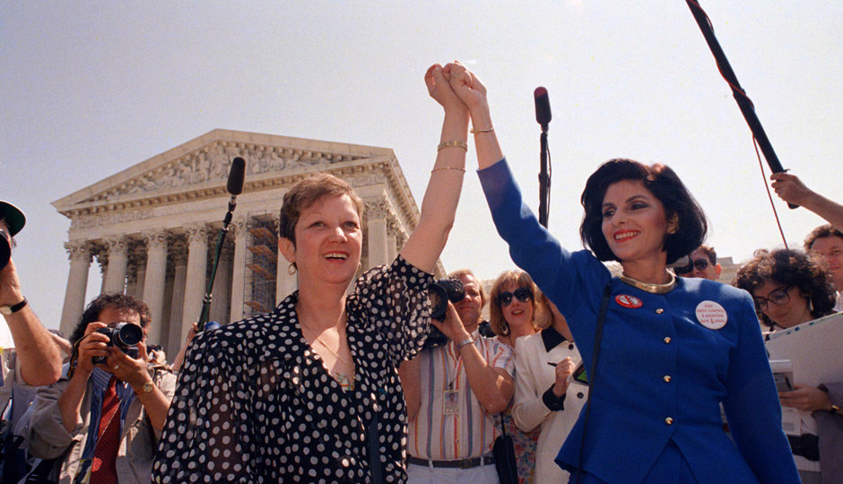 Norma McCorvey, Jane Roe in the 1973 court case, left, and her attorney Gloria Allred hold hands as they leave the Supreme Court building in Washington, DC., Wednesday, April 26, 1989 after sitting in while the court listened to arguments in a Missouri abortion case. The court's decision may overturn the 1973 Roe v Wade case which legalized abortion. (AP Photo/J. Scott Applewhite)