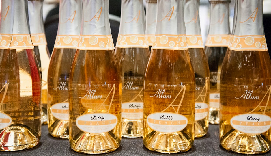 Mini bottles of peach bubbly greeted guests as they entered the event. Photo by Christina Lee for Ashley Lynn Fry Photography.