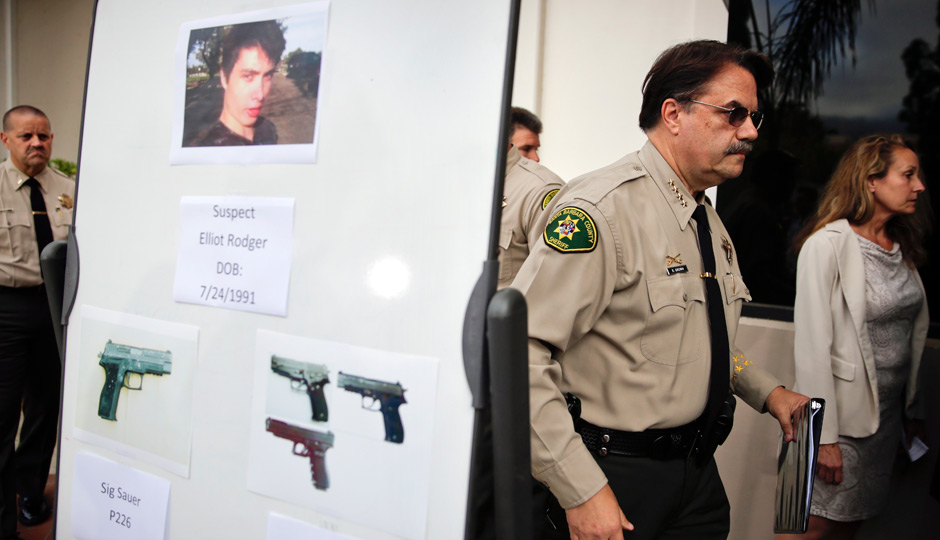 Santa Barbara County Sheriff Bill Brown, right, walks past a board showing the photos of suspected gunman Elliot Rodger and the weapons he used in Friday night's mass shooting that took place in Isla Vista, Calif., after a news conference on Saturday, May 24, 2014, in Santa Barbara, Calif. Sheriff's officials say Rodger, 22, went on a rampage near the University of California, Santa Barbara, stabbing three people to death at his apartment before shooting and killing three more in a crime spree through a nearby neighborhood. (AP Photo | Jae C. Hong)