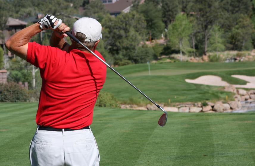 Golfer hitting ball on green, focus on golfer