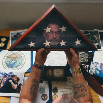 Charlie Strange holds the flag given to him by the military after his son's death. Photography by Neal Santos