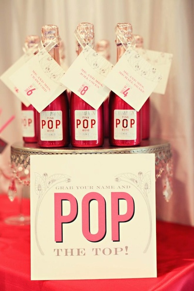 Mini champagne bottles double as escort-card holders and favors.