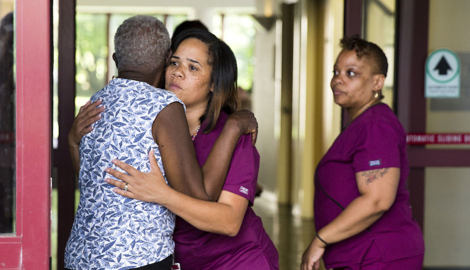 A hospital worker embraces a woman near the scene of a shooting at the Mercy Fitzgerald Hospital in Darby, Pa. on Thursday, July 24, 2014. A prosecutor said a gunman opened fire inside the psychiatric unit leaving one hospital employee dead and a second injured before being critically wounded himself. (AP Photo)