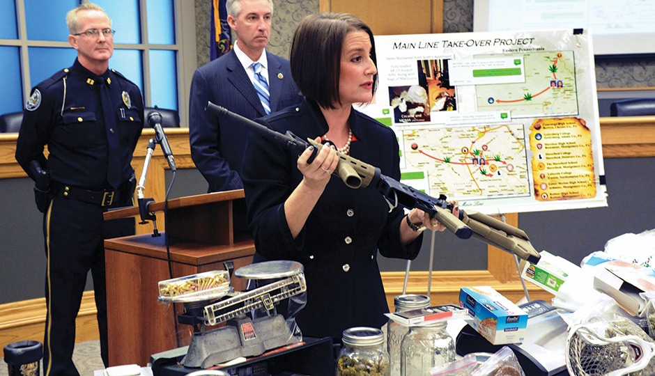 Montco D.A. Risa Ferman with an AR-15 rifle and drugs seized by the police.  / Associated Press