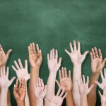 shutterstock_hands-raised-school-chalkboard-940x540