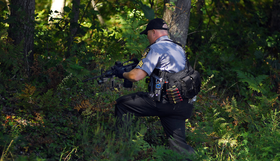 A Pennsylvania State Trooper walks into a wooded area as investigators return to scour the woods across the street from the state police barracks on Sunday, Sept. 14, 2014, in Blooming Grove Township, Pa. On Friday night, State Trooper Cpl. Bryon Dickson, 38, of Dunmore, Pa.,was killed and Trooper Alex T. Douglass, 31, of Olyphant, Pa., was wounded after a shooting ambush at the barracks. No arrests have been made yet.  (AP Photo/The Scranton Times-Tribune, Butch Comegys)