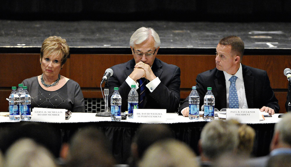 Central Bucks School Board Member Geryld McMullen (left), Dr. David Weitzel, Superintendent for Central Bucks School District (middle) and Paul Faulner, School Board President listen to public comment on the recent hazing scandal which caused the cancellation of the 2014 football season with two games left.