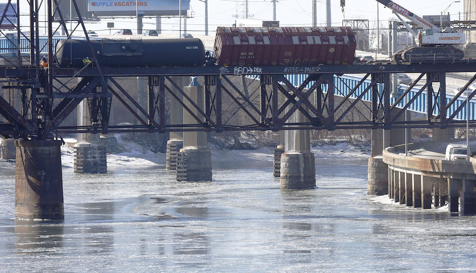 Railroad crews work on one of five derailed tank cars on a bridge over the Schuylkill River, January in Philadelphia. The accident Monday followed a series of derailments involving Bakken Shale crude from North Dakota including one that exploded in Canada, killing 47 people. (AP Photo/Matt Rourke)