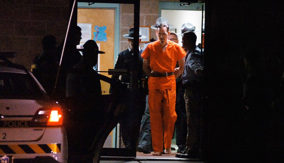 Pennsylvania State Police Troopers take away suspected killer Eric Frein from the Blooming Grove State Police barracks early Friday, Oct. 31, 2014, in Blooming Grove Township, Pennsylvania.  (AP Photo /The Scranton Times-Tribune, Butch Comegys)