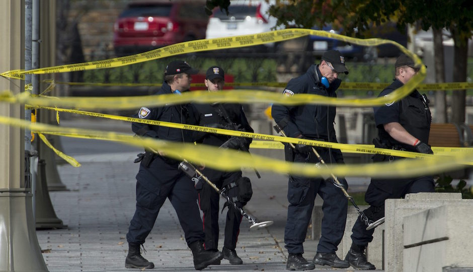 Police with metal detectors comb the area near the National War Memorial near Parliament Hill, where Cpl. Nathan Cirillo, 24, was killed by a gunman, in Ottawa on Thursday, Oct. 23, 2014. A gunman opened fire at the National War Memorial, then moved to nearby Parliament Hill and wounded a security guard before he was shot, reportedly by Parliament's sergeant-at-arms on Wednesday.  (AP Photo/The Canadian Press, Justin Tang)