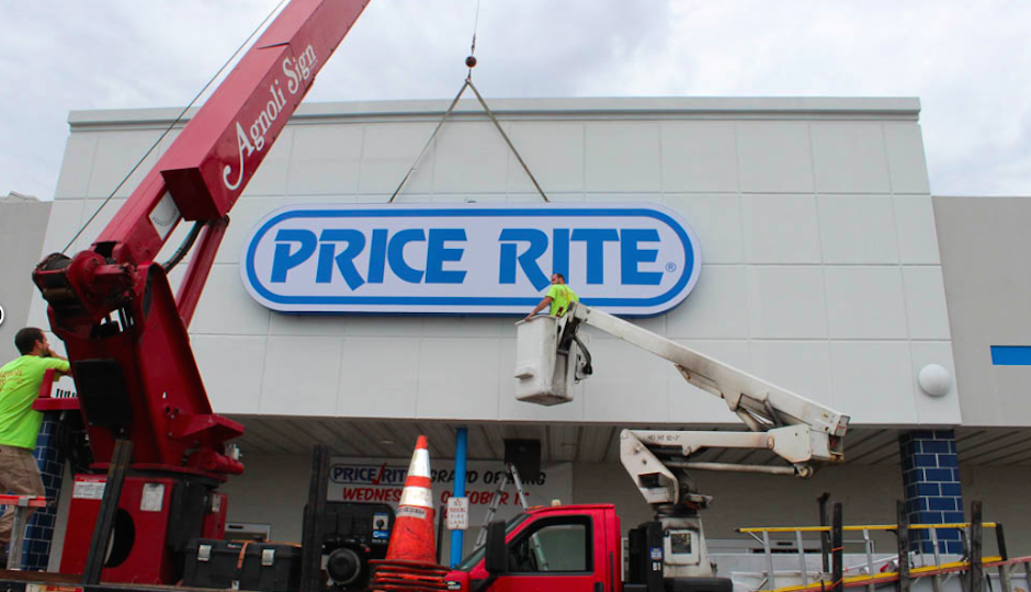 Workers lower the PriceRite sign into place ahead of this week's store opening in Camden.