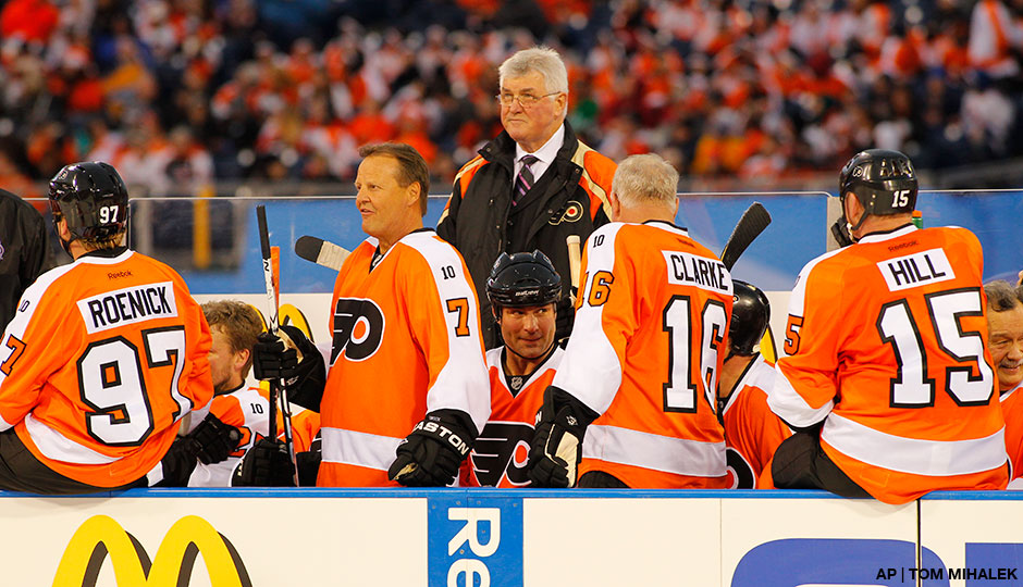 Members of the Philadelphia Flyers Alumni team, from the left, Bill Barber, Eric Lindros, Bob Clarke and coach Pat Quinn (standing) on the bench during the Winter Classic Alumni hockey game with the New York Rangers Alumni team, Saturday, Dec. 31, 2011 in Philadelphia.  AP | Tom Mihalek