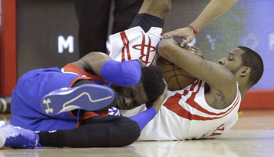 Philadelphia 76ers' Nerlens Noel, left, holds his head after scrambling for a ball against Houston Rockets' Trevor Ariza, right, in the second half of an NBA basketball game Friday, Nov. 14, 2014, in Houston. The Rockets won 88-87.(AP Photo/Pat Sullivan)