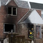 Firefighters enter a burned-out home in the aftermath of a fatal fire Tuesday, Dec. 9, 2014, in Philadelphia. A firefighter was trapped in the basement of the burning row home early Tuesday, becoming the first female member of the Philadelphia Fire Department to die in the line of duty, officials said. The 11-year veteran was part of the first company deployed to a fire in the basement of the home in the city's West Oak Lane neighborhood at about 3 a.m. Tuesday, fire commissioner Derrick Sawyer said.