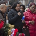 Emerald Garner, daughter of Eric Garner, center, visits a makeshift memorial near the site where NYPD officers Rafael Ramos and Wenjian Liu were murdered in the Brooklyn borough of New York, Monday, Dec. 22, 2014. Police say Ismaaiyl Brinsley ambushed the two officers in their patrol car in broad daylight Saturday, fatally shooting them before killing himself inside a subway station. (AP Photo/John Minchillo)