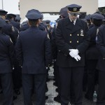 Some police officers, left, turn their backs in a sign of disrespect as Mayor Bill de Blasio speaks as others, at right front line, stand at attention, during the funeral of New York Police Department Officer Wenjian Liu at Aievoli Funeral Home, Sunday, Jan. 4, 2015, in the Brooklyn borough of New York. Liu and his partner, officer Rafael Ramos, were killed Dec. 20 as they sat in their patrol car on a Brooklyn street. The shooter, Ismaaiyl Brinsley, later killed himself. (AP Photo/John Minchillo)