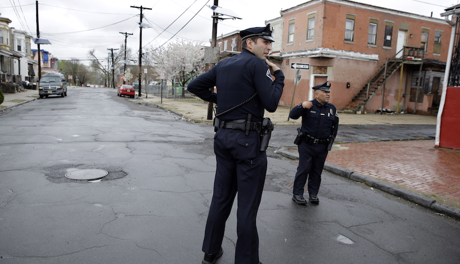 In this April 15, 2014 file photo, Camden County Metro police officers Lucas Murray, left, and Daniel Torres react to what they thought was a gunshot, but turned out to be a car backfiring, as they patrol a neighborhood in Camden, N.J.  The crime rate always fluctuates, but recent improvements in Camden are getting major attention because of the circumstances. The city's old police department was dissolved in 2013 and replaced with a force run by the county government. With lower costs per officer, the new force is bigger, allowing for more beat-driven police work and preventative policing. (AP Photo/Mel Evans, File)