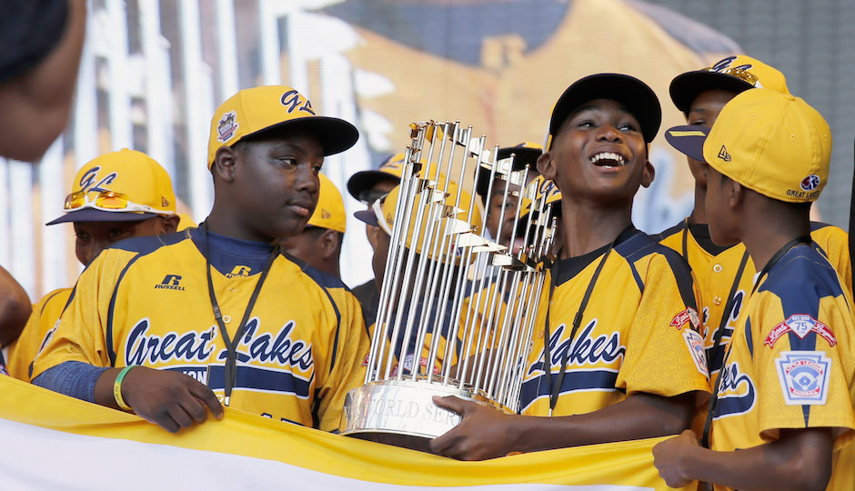 In this Aug. 27, 2014, file photo, members of the Jackie Robinson West Little League baseball team participate in a rally in Chicago celebrating the team's U.S. Little League Championship. Little League International has stripped Chicago's Jackie Robinson West team of its national title after finding the team falsified its boundary map. The league made the announcement Wednesday morning, Feb. 11, 2015, saying the Chicago team violated regulations by placing players on the team who didn't qualify because they lived outside the team's boundaries. Little League International also suspended Jackie Robinson West manager Darold Butler from league activity.(AP Photo/Charles Rex Arbogast, File)