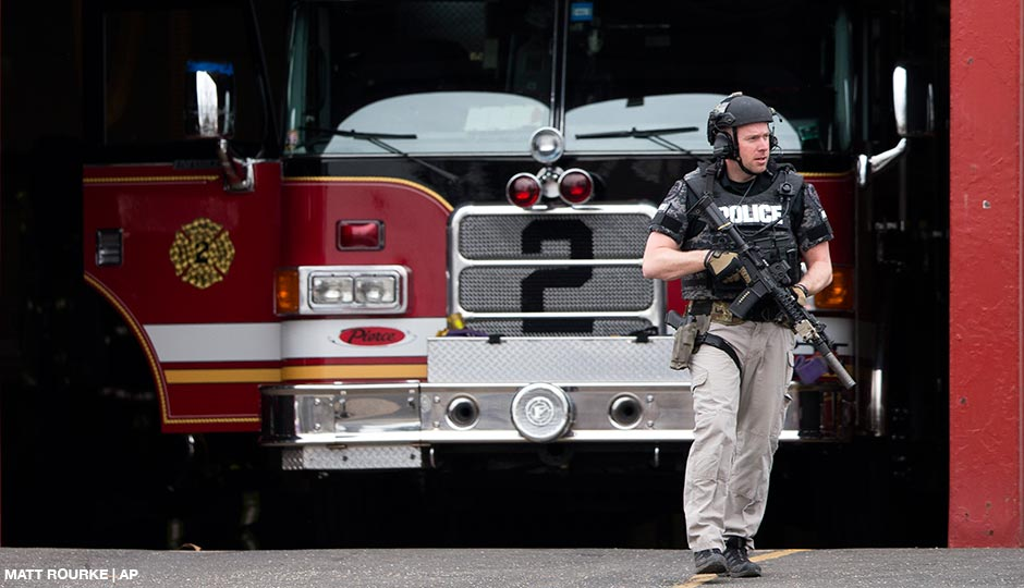 An officer walks out of the LaMott Fire Company after police escorted a man away, Tuesday, March 31, 2015, in Elkins Park, Pa. Authorities say a former volunteer firefighter held four firefighters hostage at the Philadelphia-area firehouse before surrendering to police. No injuries were reported.