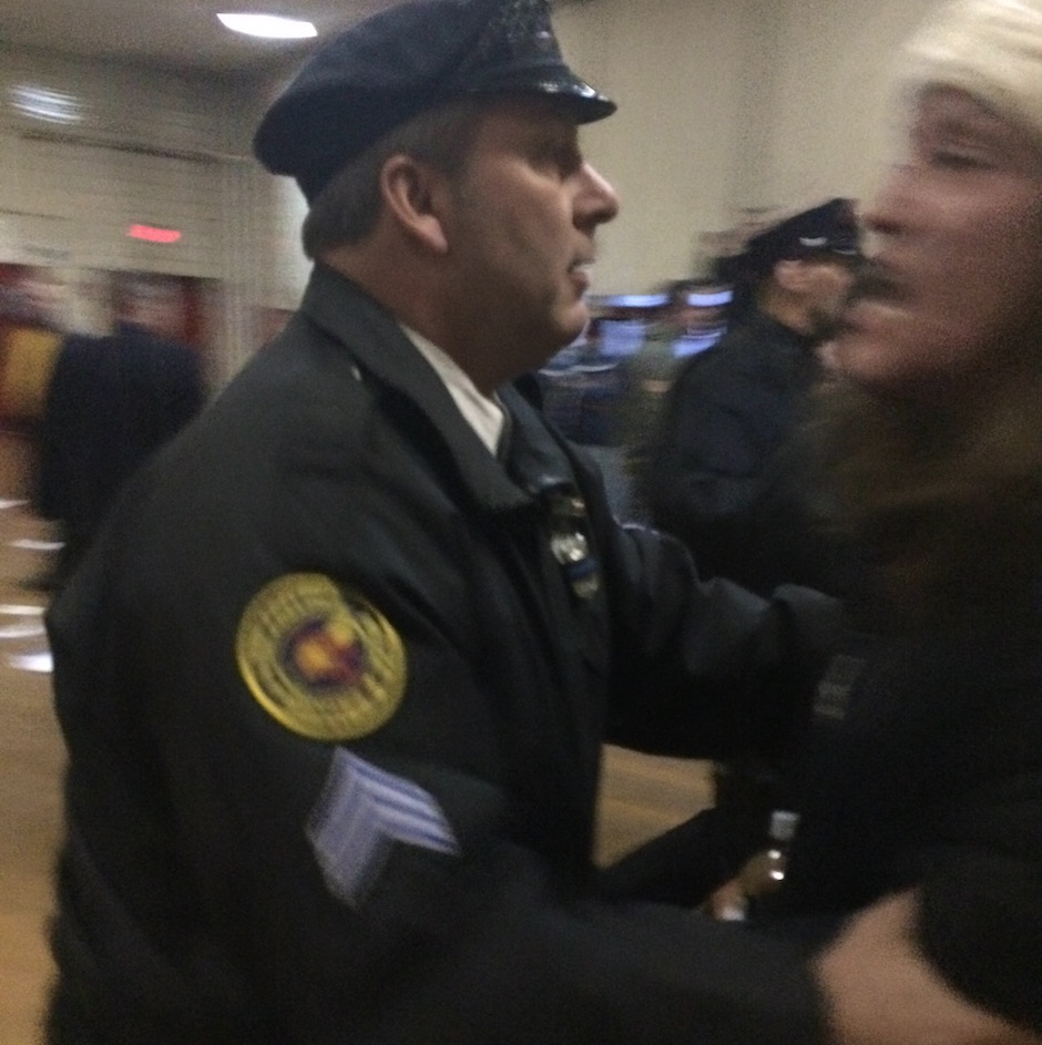 A Philadelphia Police officer shoves a protester toward the exit, Thursday night at Lawncrest Recreation Center.