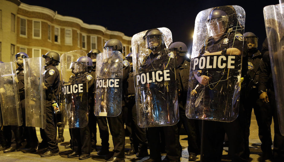Police stand in formation as a curfew approaches, Tuesday, April 28, 2015, in Baltimore, a day after unrest that occurred following Freddie Gray's funeral. (AP Photo/Patrick Semansky)