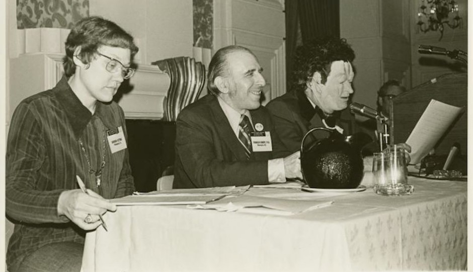 Barbara Gittings at a hearing with Frank Kameny, and John E. Fryer. Also known as Doctor Anonymous, Fryer is credited with championing the American Psychiatric Association's decision to remove homosexuality from the Diagnostic and Statistical Manual of Mental Disorders. Photo was taken in 1972.