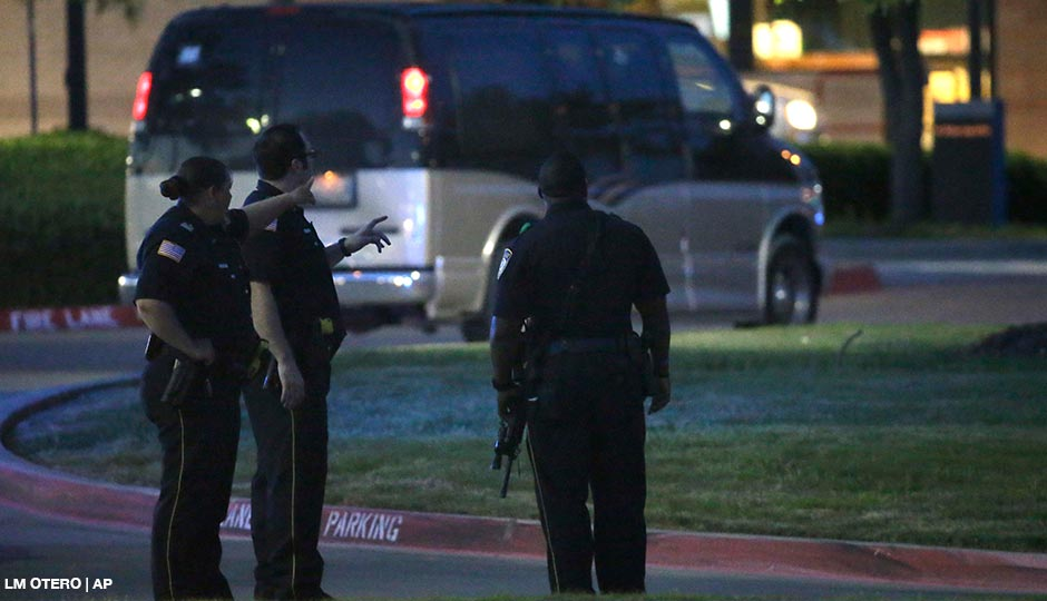 Police officers stands guard at a parking lot near the Curtis Culwell Center where a provocative contest for cartoon depictions of the Prophet Muhammad was held Sunday, May 3, 2015, in Garland, Texas. The contest was put on lockdown Sunday night and attendees were being evacuated after authorities reported a shooting outside the building.
