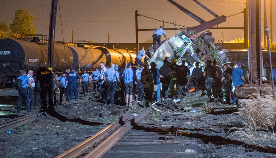 Emergency responders work on an overturned Amtrak car near tanker cars on May 12, 2015. Photograph by Bryan Woolston
