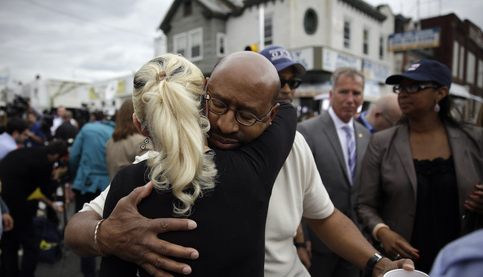 Philadelphia Mayor Michael Nutter, center right, hugs Lori Dee Patterson, a nearby resident, after she handed him a cup of coffee after he spoke at a news conference near the scene of a deadly train derailment, Wednesday, May 13, 2015, in Philadelphia. An Amtrak train headed to New York City derailed and crashed in Philadelphia on Tuesday night, killing at least six people and injuring dozens more. (AP Photo/Matt Slocum)xx