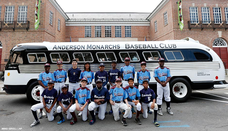 Members of the 2014 Taney Little League-Anderson Monarchs teams pose for a photo with their team bus in front of the Baseball Hall of Fame on Thursday, Sept. 25, 2014, in Cooperstown, N.Y. Pitcher Mo'ne Davis is fourth from left.