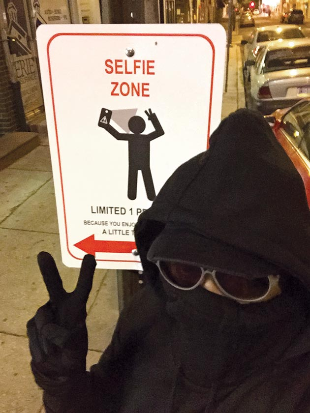 Street artist Kid Hazo with a sign he designed at 5th and Bainbridge streets, May 6, 2015.