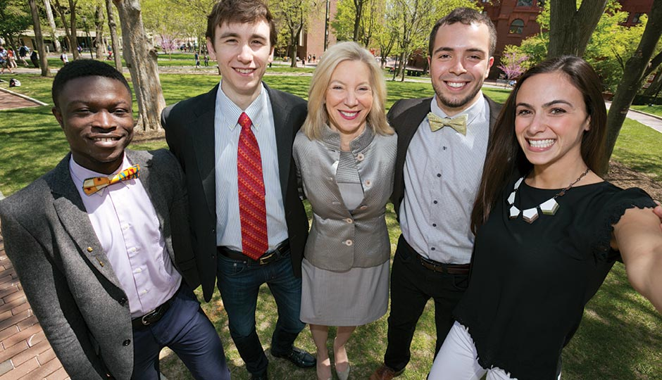 Amy Gutmann with four graduating seniors on College Green, April 29, 2015.