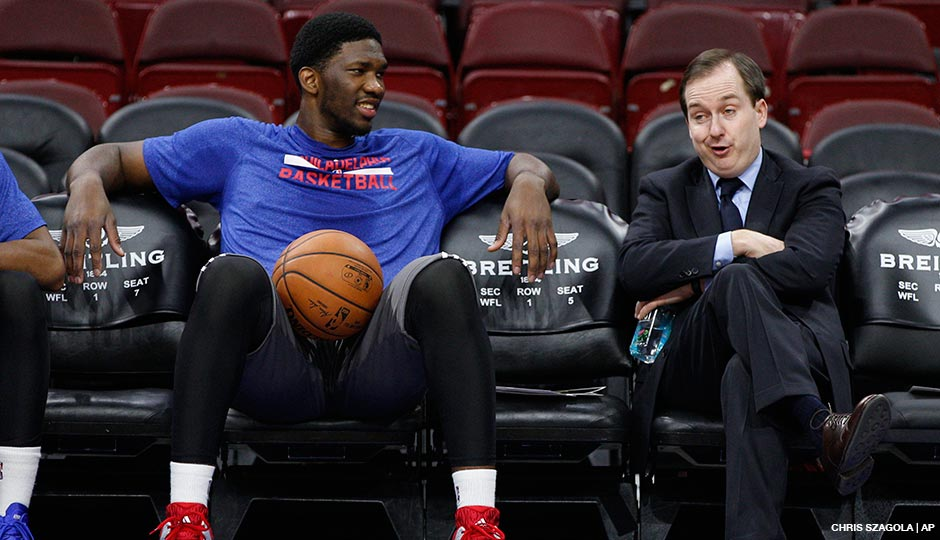 76ers general manager Sam Hinkie (right) talks with center Joel Embiid during pre-game warm-ups at the Wells Fargo Center on December 15th, 2014.