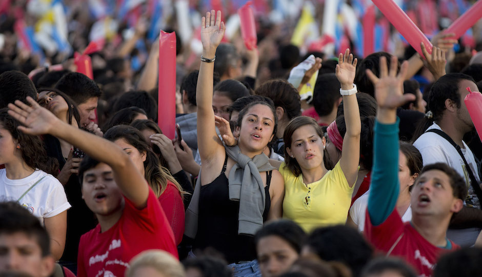 People pray and sing before Pope Francis arrives to a meeting with the young in Asuncion, Paraguay, Sunday, July 12, 2015. The Pope addressed tens of thousands of young people waiting for him at a venue along the banks of the Paraguay River. Up to 2 million people are expected in Philadelphia for the pope's September visit (AP Photo/Natacha Pisarenko)