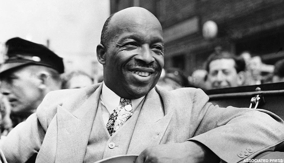 African American spiritual leader Father Divine smiles as he leads a parade of his followers from Harlem to the docks in New York, on Aug. 20, 1936, to board the paddle-steamer City of Kennsburg to take them on the first stage of their great trek to their new camp in Ulster County, New York State.