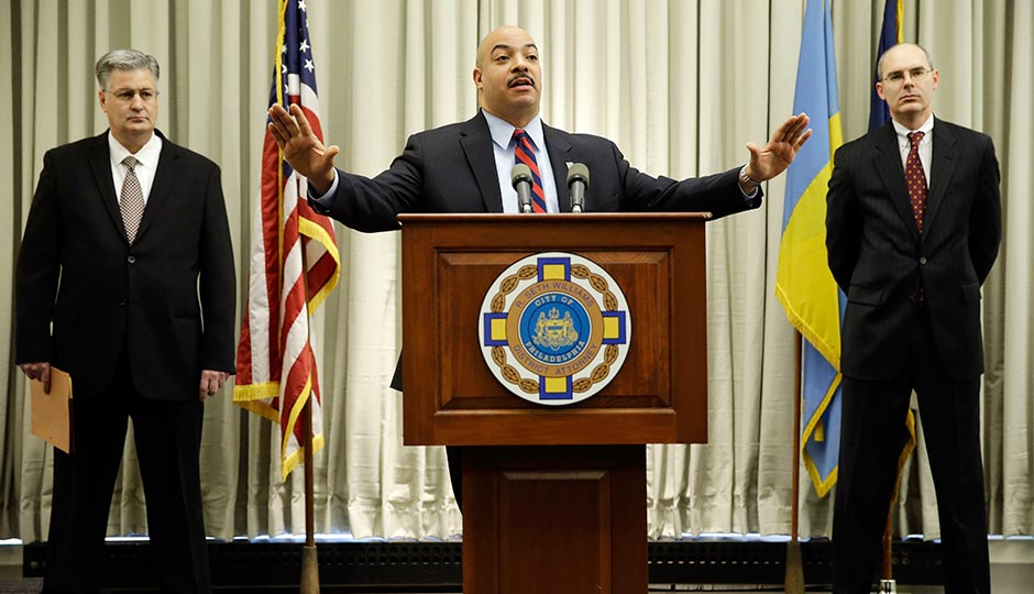 Philadelphia District Attorney Seth Williams, center, accompanied by investigators Marc Costanzo, left, and Frank Fina, speaks during a news conference Monday, Jan. 27, 2014, in Philadelphia.