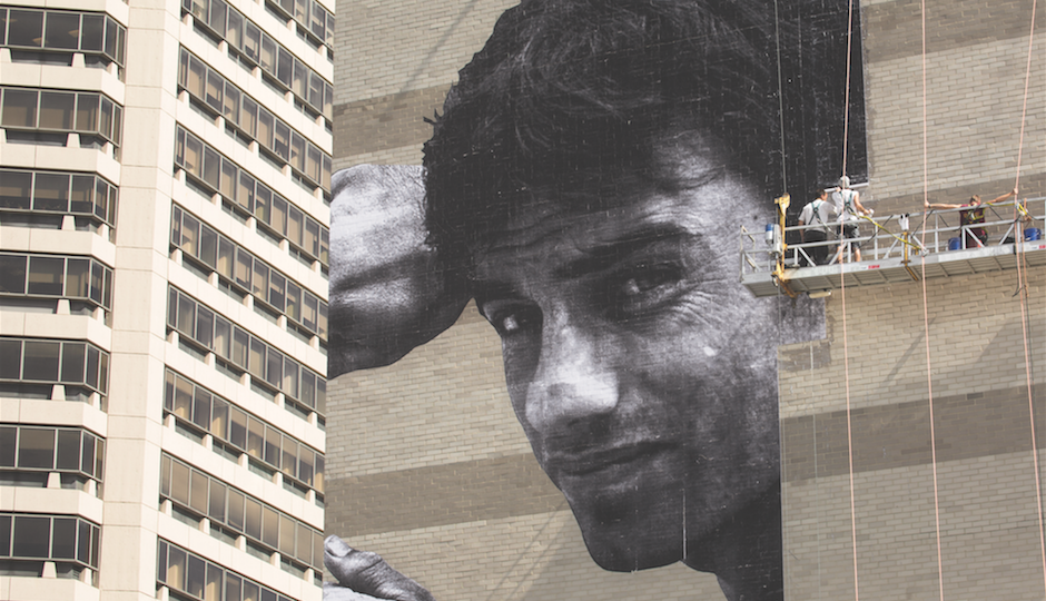 French artist JR works on his 15-story photographic creation.   Photo by Steve Weinik