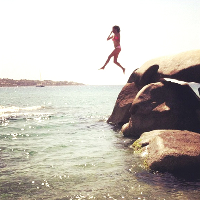 Me, holding my nose while jumping off a rock in Corsica,