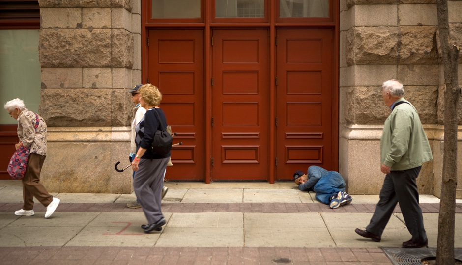 Tourists walk past a homeless person during Pope Francis' visit to Philadelphia. Photo | Bradley Maule