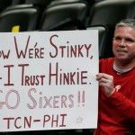 Philadelphia 76ers fan and Bucks County, Pa., native Andy Atkinson, who now lives in Denver, waves a placard in support of 76ers general manager Sam Hinkie's rebuilding effort as the Sixers take the court to face the Denver Nuggets in the first quarter of an NBA basketball game Wednesday, March 25, 2015, in Denver.