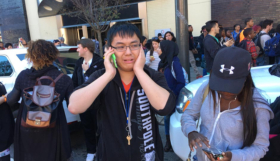 Community College of Philadelphia freshman Matthew Liu makes a phone call as students and staff gather on Spring Garden Street. Photo | Jared Shelly