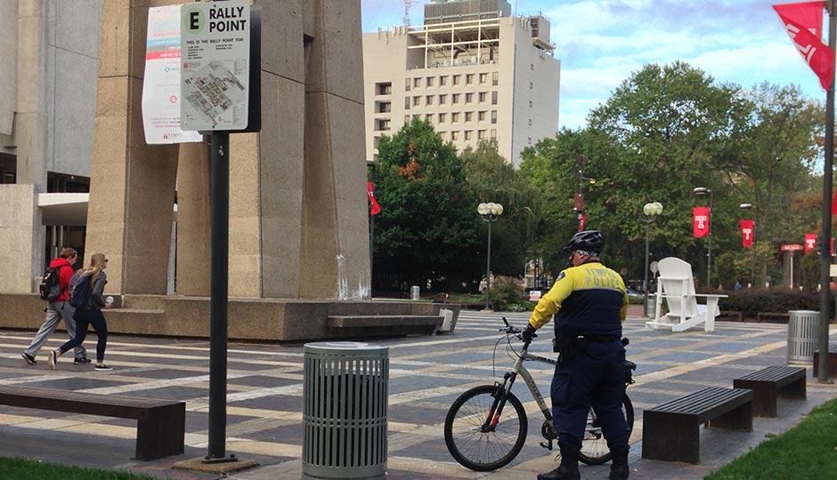 A Temple University Police Bike Officer stands guard at the Bell Tower, the epicenter of campus, earlier this morning. Photo | Rob DiRienzo