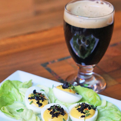 Black truffle deviled eggs and a black beer at Bru | Photo via Bru Craft & Wurst