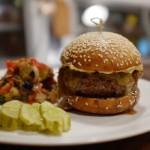 KQ Burger with raw cheddar, garlic chili aioli, served on a brioche.