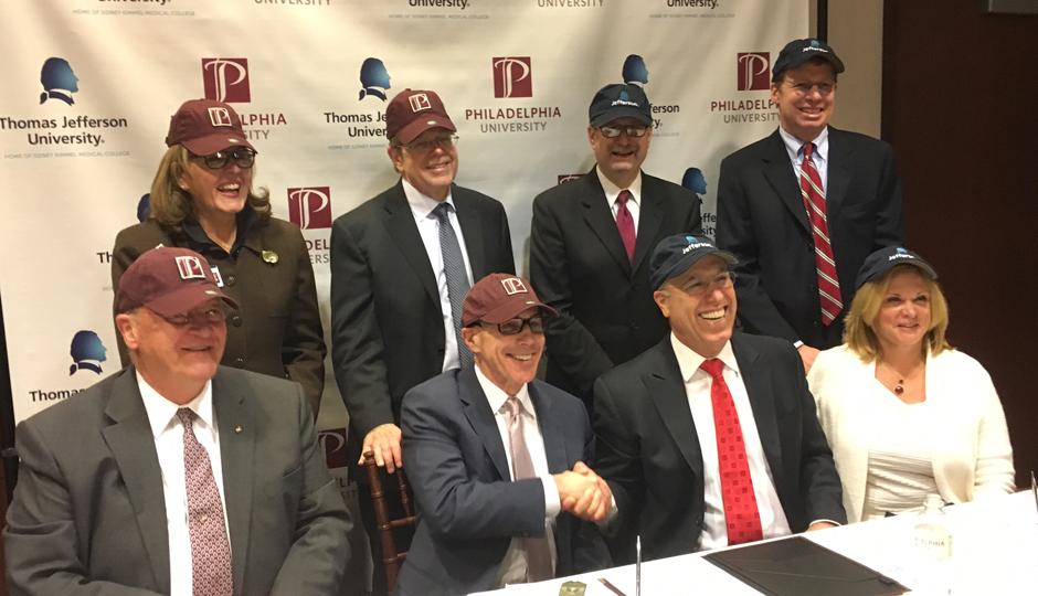 Stephen Klasko (left) shakes hands with Stephen Spinelli as Philadelphia University and Thomas Jefferson University formally announce a merger agreement.
